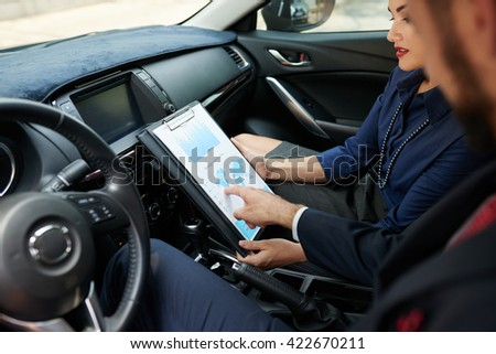 Business people analyzing chart when sitting in car