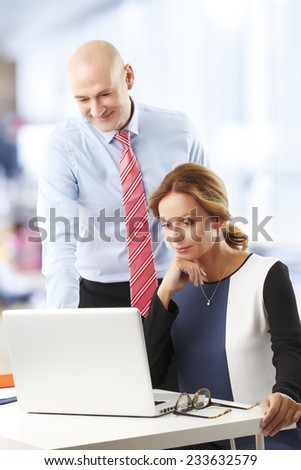 Business people analyzing data on laptop, while sitting at desk in office. - stock photo