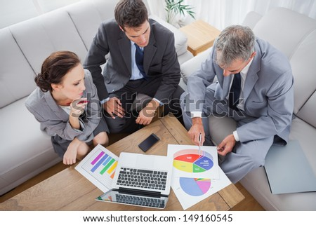 Business people analyzing diagrams together in cosy meeting room