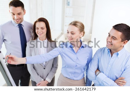 business, people and conference concept - smiling business team meeting on presentation in office - stock photo