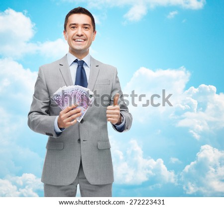 business, people and finances concept - smiling businessman with european money showing thumbs up over blue sky with clouds background - stock photo