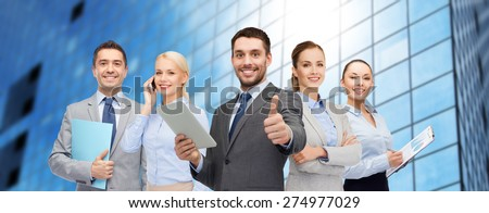 business, people and gesture concept - group of smiling businessmen showing thumbs up over office building background - stock photo