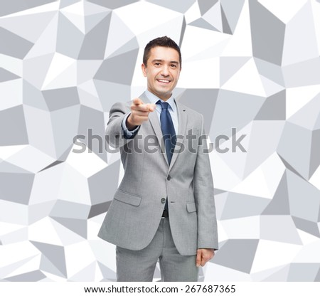 business, people and gesture concept - happy smiling businessman in suit pointing at you over gray graphic low poly background - stock photo