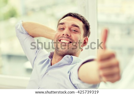 business, people and gesture concept - smiling man showing thumbs up at home or office - stock photo