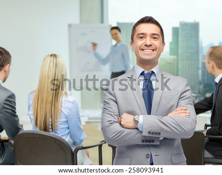 business, people and office concept - happy businessman with team at presentation over office room background - stock photo