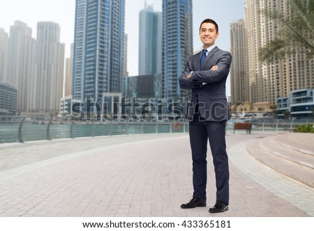 business, people and office concept - happy smiling businessman in dark grey suit over dubai city street background - stock photo