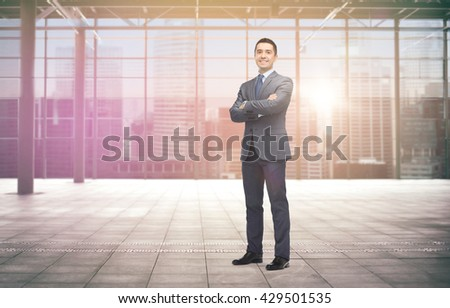 business, people and office concept - happy smiling businessman in dark grey suit over empty hall and city background - stock photo
