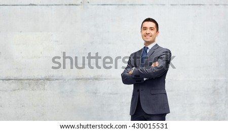 business, people and office concept - happy smiling businessman in dark grey suit over gray concrete wall background - stock photo