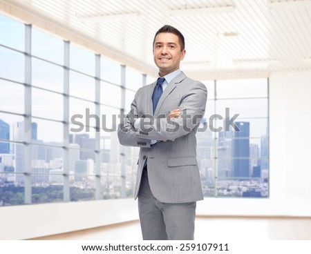 business, people and office concept - happy smiling businessman in suit over room and window with city view background - stock photo
