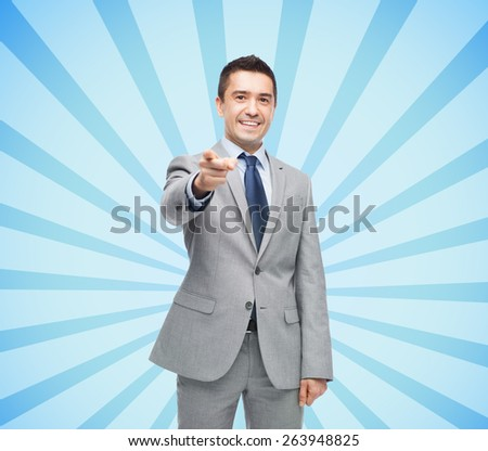 business, people and office concept - happy smiling businessman in suit pointing at you over blue burst rays background - stock photo