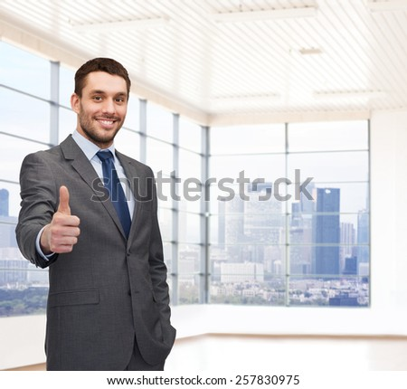 business, people and office concept - happy young businessman showing thumbs up over office room or new apartment background - stock photo