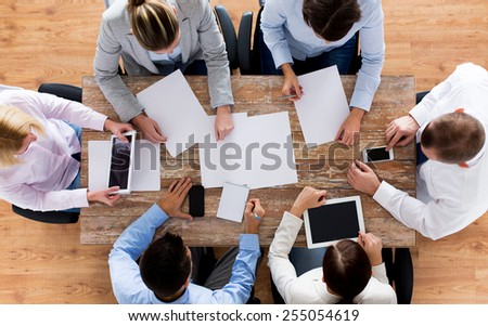 business, people and team work concept - close up of creative team with papers and gadgets meeting in office - stock photo