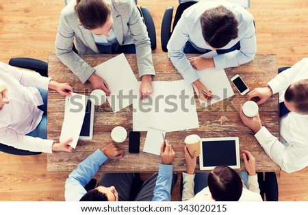 business, people and team work concept - close up of creative team with papers and gadgets meeting and drinking coffee in office