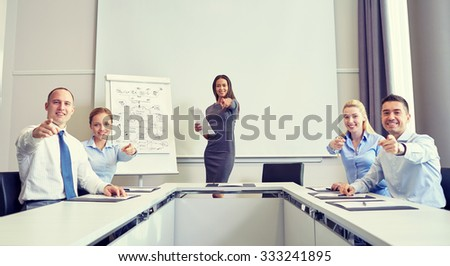 business, people and teamwork concept - group of smiling businesspeople meeting and pointing finger at you in office - stock photo