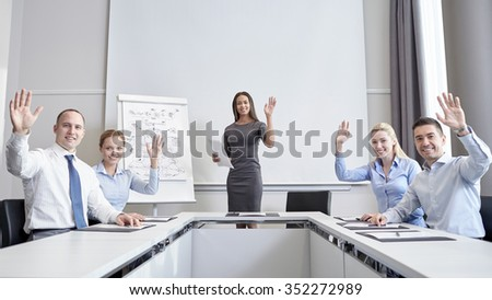 business, people and teamwork concept - group of smiling businesspeople meeting and waving hands in office - stock photo