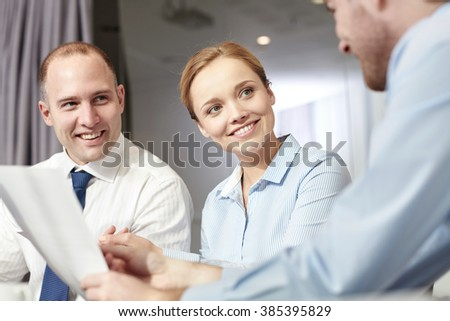 business, people and teamwork concept - smiling business team with papers meeting and talking in office - stock photo