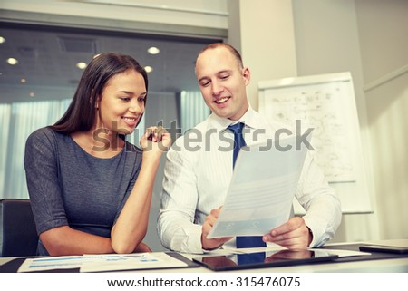 business, people and teamwork concept - smiling businessman and businesswoman with papers meeting in office