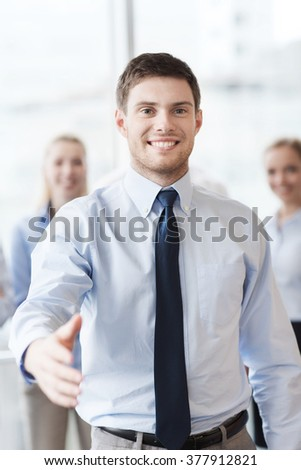 business, people and teamwork concept - smiling businessman making handshake gesture with group of businesspeople in office
