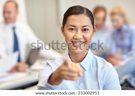 business, people and teamwork concept - smiling businesswoman pointing finger at you with group of businesspeople meeting in office - stock photo