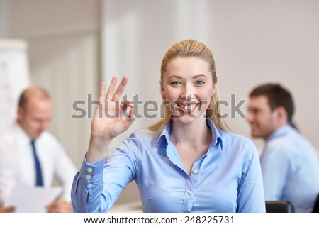 business, people and teamwork concept - smiling businesswoman showing ok gesture with group of businesspeople meeting in office