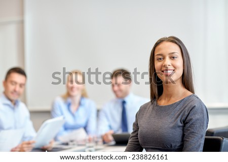 business, people and teamwork concept - smiling businesswoman with group of businesspeople meeting in office - stock photo