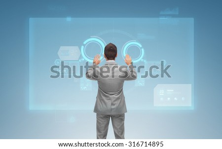 business, people and technology concept - businessman touching virtual screens over blue background from back