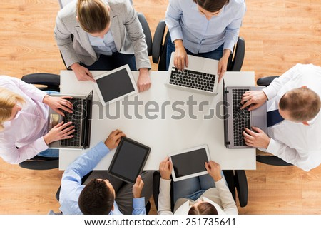 business, people and technology concept - close up of creative team with laptop and tablet pc sitting at table in office - stock photo