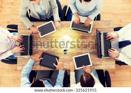 business, people and technology concept - close up of creative team with laptop and tablet pc sitting at table in office over lighting bulb - stock photo