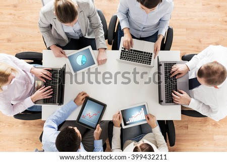 business, people and technology concept - close up of creative team with laptop and tablet pc computers displaying charts on screens sitting at table in office - stock photo