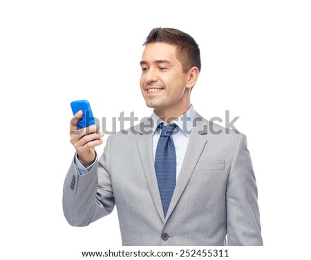 business, people and technology concept -happy businessman texting on smartphone - stock photo
