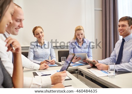 business, people and technology concept - happy businesspeople with tablet pc computers meeting in office - stock photo