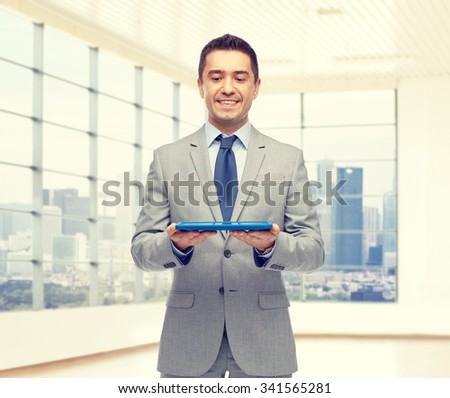business, people and technology concept - happy smiling businessman in suit holding tablet pc computer over office room background - stock photo
