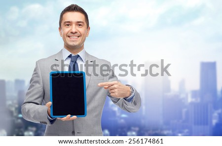 business, people and technology concept - happy smiling businessman in suit showing tablet pc computer black blank screen over city background - stock photo