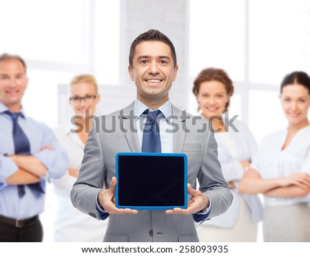 business, people and technology concept - happy smiling businessman with team showing tablet pc computer black blank screen over office room background - stock photo