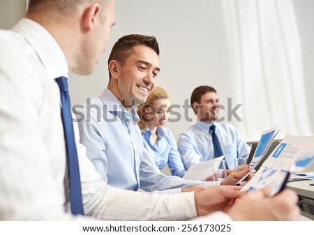 business, people and technology concept - smiling business team with laptop computer, papers and smartphone meeting in office - stock photo
