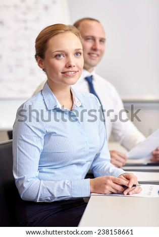business, people and technology concept - smiling business team with papers meeting in office - stock photo