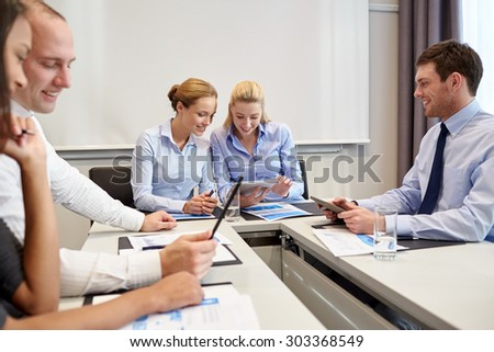 business, people and technology concept - smiling business team with tablet pc computers and papers meeting in office - stock photo