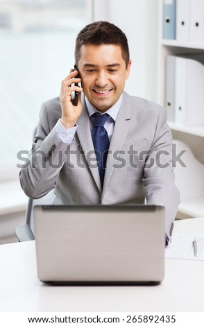 business, people and technology concept - smiling businessman with laptop computer calling on smartphone in office
