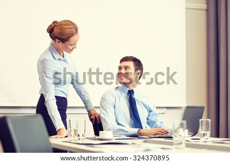 business, people and work concept - businessman and secretary with laptop working in office - stock photo