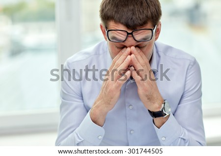 business, people and work concept - tired businessman with eyeglasses in office - stock photo