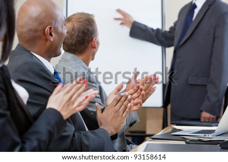 Business people applauding after speech of a businessman at the conference - stock photo