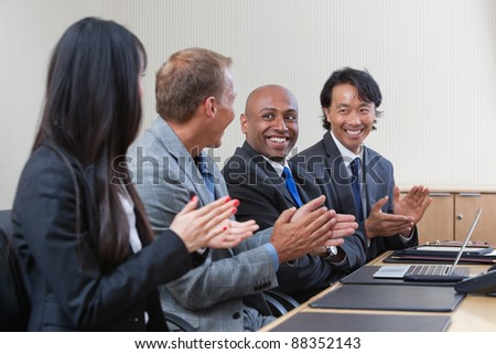 Business people applauding and smiling in presentation room - stock photo