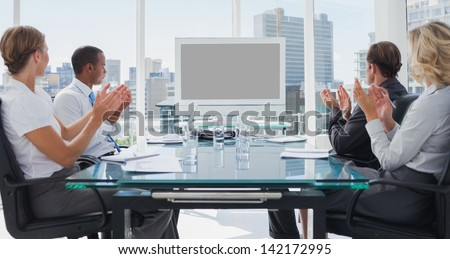 Business people applauding during a video conference in the boardroom - stock photo