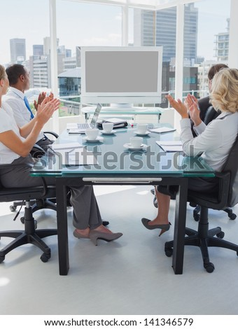 Business people applauding during a video conference while they are sat in the boardroom - stock photo