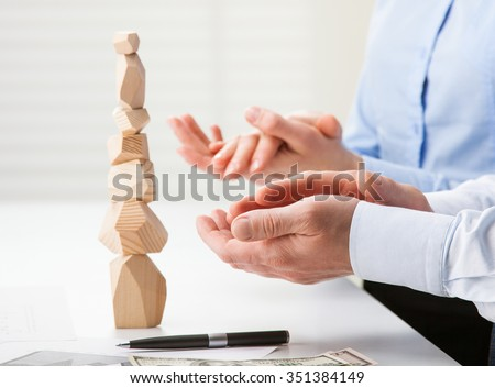 Business people applauding near built wooden tower (Japanese game tumi-ishi), illustrating concept of business success, cooperation, achievement and self-control - stock photo