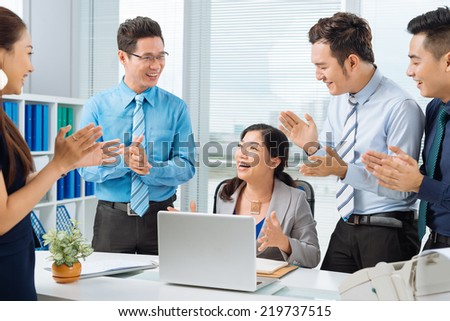 Business people applauding successful female colleague - stock photo