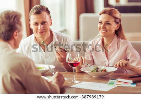 Business people are discussing business affairs, eating and smiling during business lunch at the restaurant