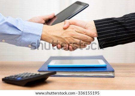 business people are handshaking after watching  business data and information on tablet computer - stock photo