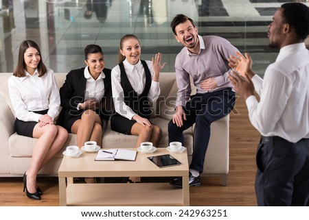 Business people are interacting and drinking coffee in the office. - stock photo