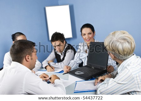 Business people around a table using a laptop and having an conversation at meeting - stock photo